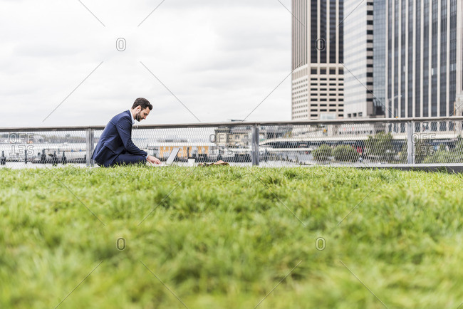 USA- New York- Manager in Manhattan sitting outdoor- using laptop and earphones