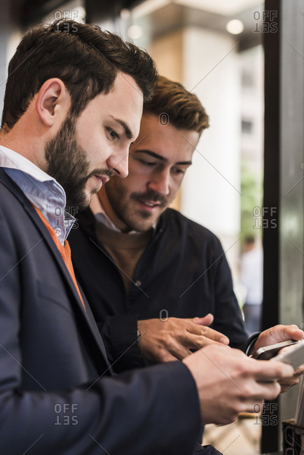 USA- New York City- Businessmen checking mobile devices