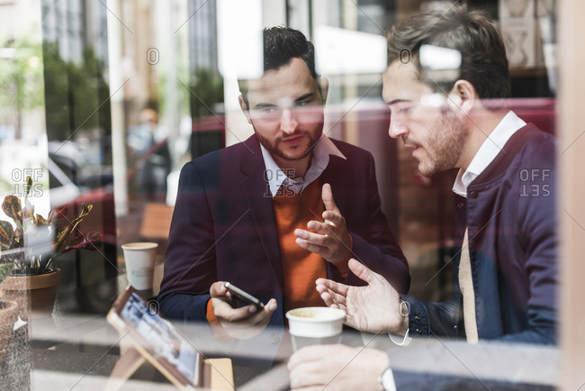 USA- New York City- Businessmen meeting in coffee shop- using mobile devices
