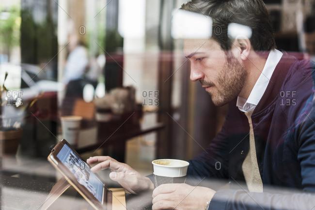 USA- New York City- Businessman sitting in coffee shop- using digital tablet