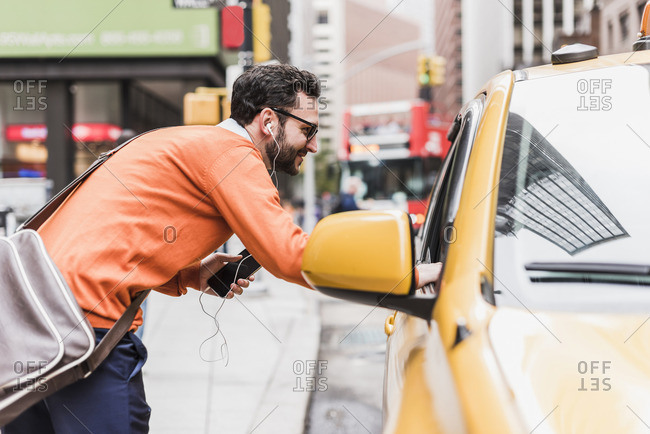 USA- New York City- Businessman talking to cab driver
