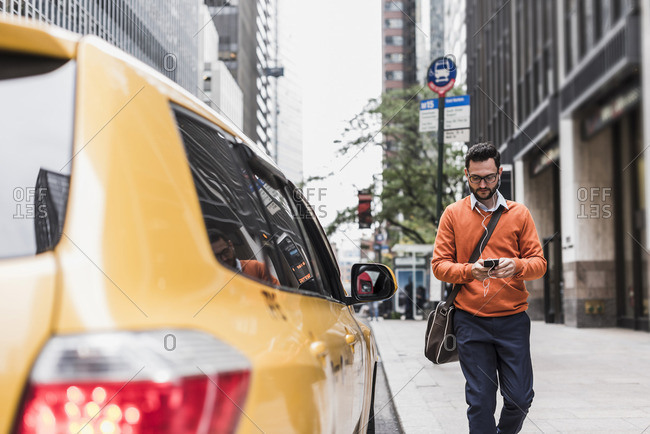 USA- New York City- Businessman approaching cab- using smart phone