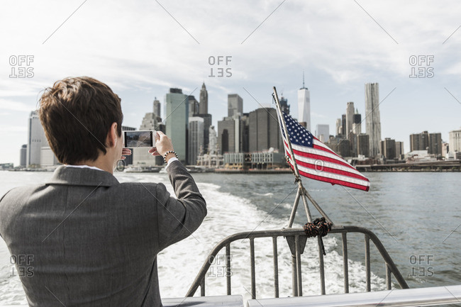USA- Brooklyn- back view of businesswoman on a boat taking picture of Manhattan skyline