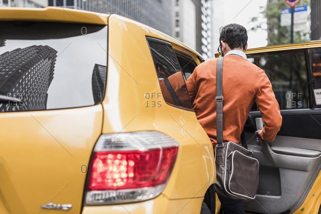 USA- New York City- Businessman entering cab