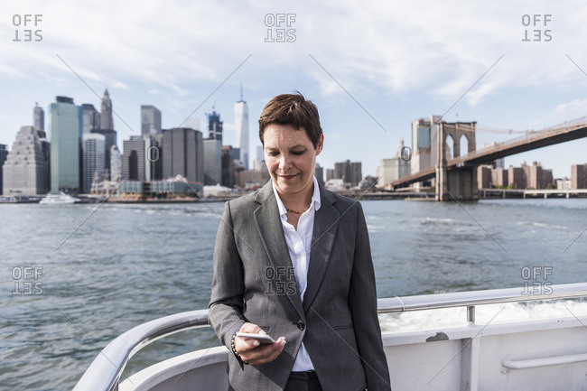 USA- Brooklyn- portrait of  businesswoman standing on boat looking at cell phone