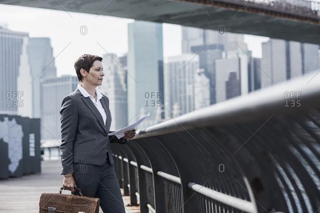 USA- Brooklyn- businesswoman standing in front of Manhattan skyline