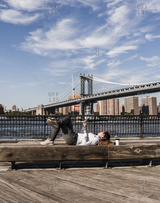 USA- Brooklyn- businesswoman lying on bench listening music with earphones