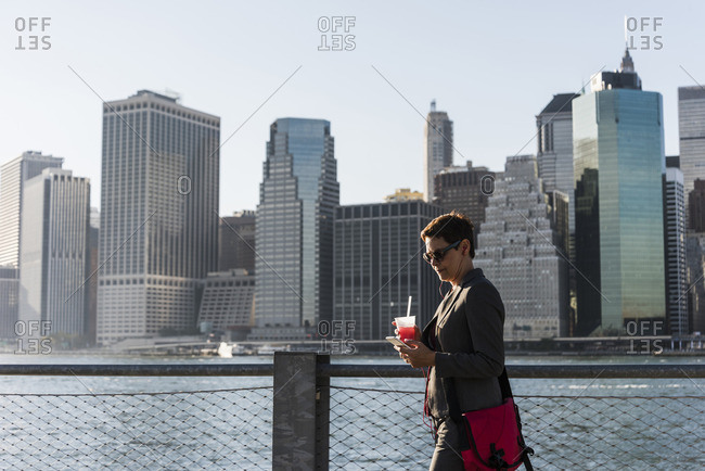 USA- Brooklyn- businesswoman looking at her smartphone in front of Manhattan skyline