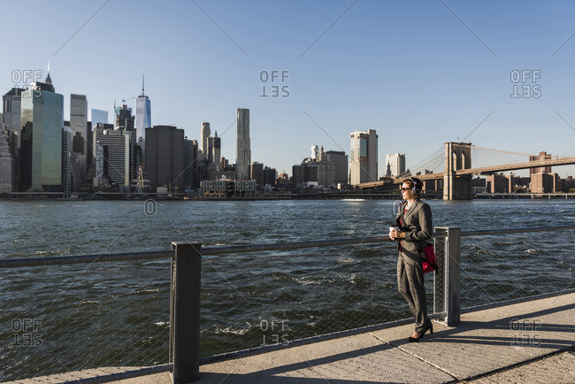 USA- Brooklyn- businesswoman with headphones looking at Manhattan skyline