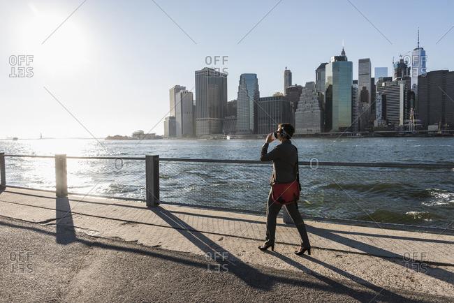 USA- Brooklyn- businesswoman drinking coffee to go in front of Manhattan skyline