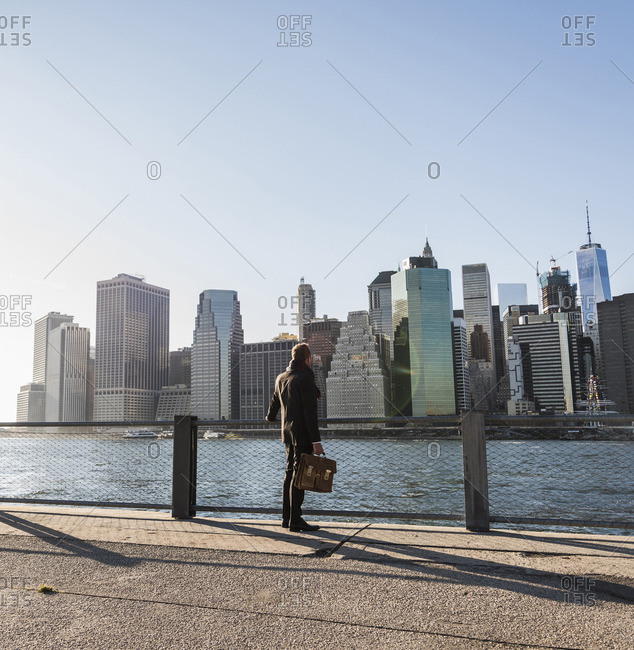 USA- Brooklyn- back view of businessman with briefcase standing in front of Manhattan skyline