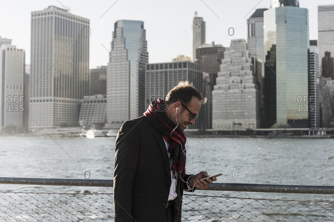 USA- Brooklyn- businessman with smartphone and earphones in front of Manhattan skyline