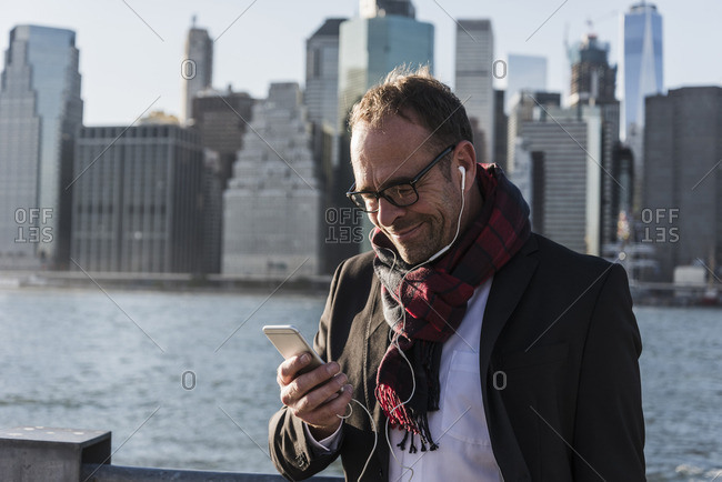 USA- Brooklyn- smiling businessman with earphones looking at his smartphone