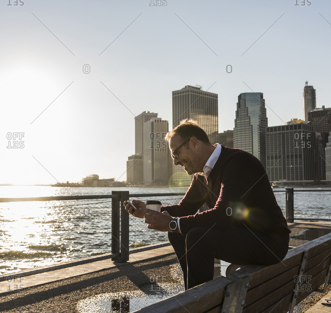 USA- Brooklyn- smiling man with coffee to go sitting on bench looking at smartphone