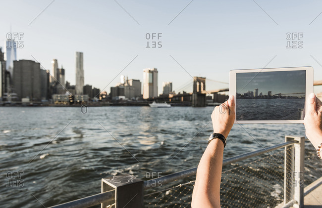 USA- Brooklyn- woman taking picture of Manhattan skyline with tablet- close-up