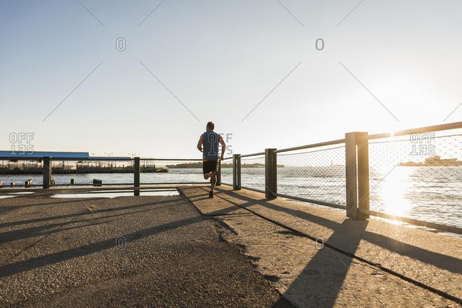 USA- Brooklyn- back view of man jogging at evening twilight