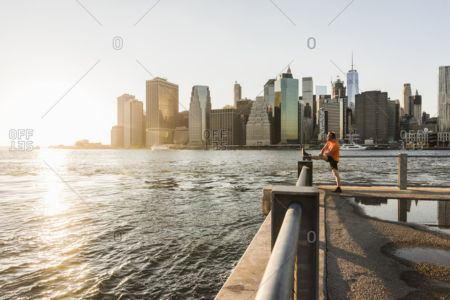 USA- Brooklyn- man doing stretching exercises in front of Manhattan skyline in the evening
