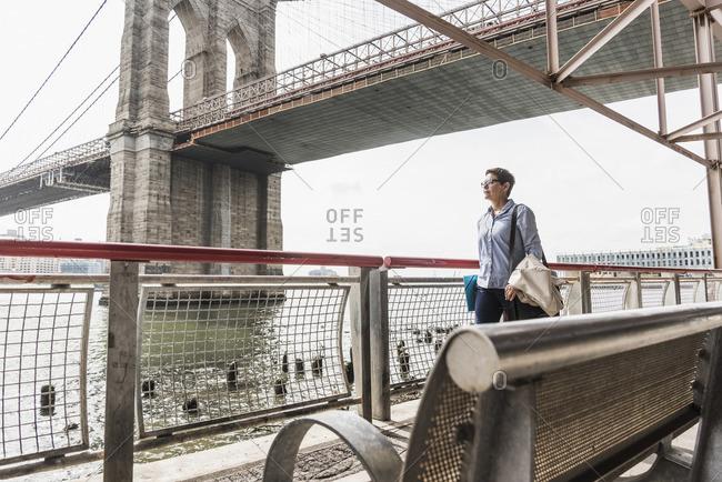 USA- New York City- woman walking at East River