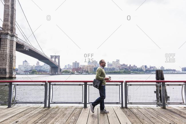 USA- New York City- man walking at East River