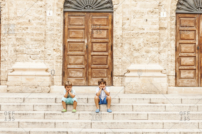 Two little boys sitting on stairs of an old building