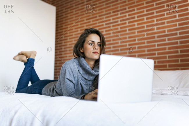 Young woman lying on bed using laptop