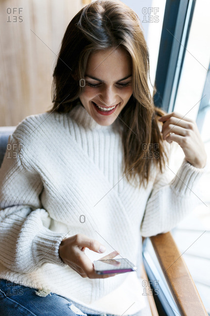 Happy young woman looking at cell phone at a window
