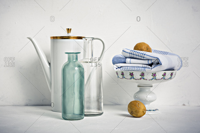Still life with coffee pot- glass bottles- bowl- towel and lemons