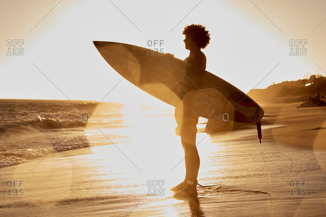 Young man holding surfboard on the beach at sunset