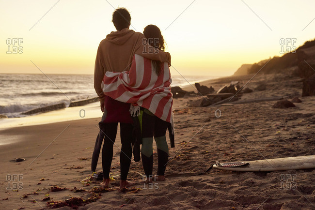 Couple embracing on the beach at sunset next to surfboard