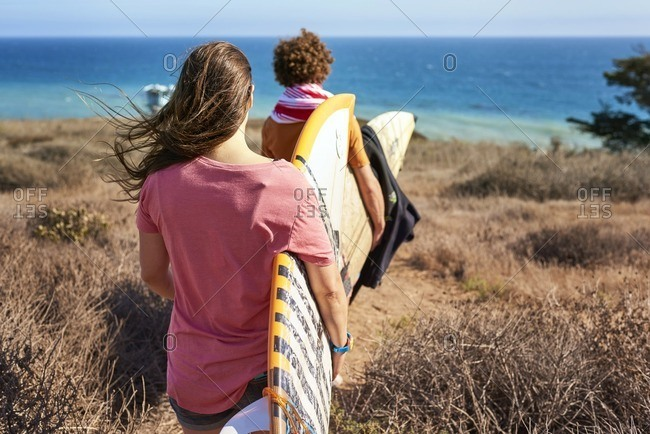Couple carrying surfboards at the coast