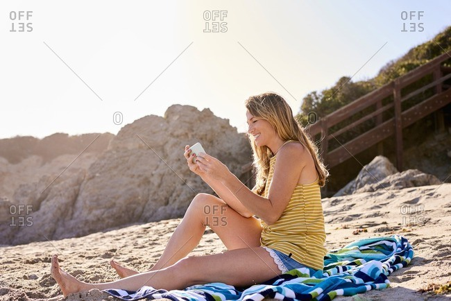 Young woman checking cell phone on the beach