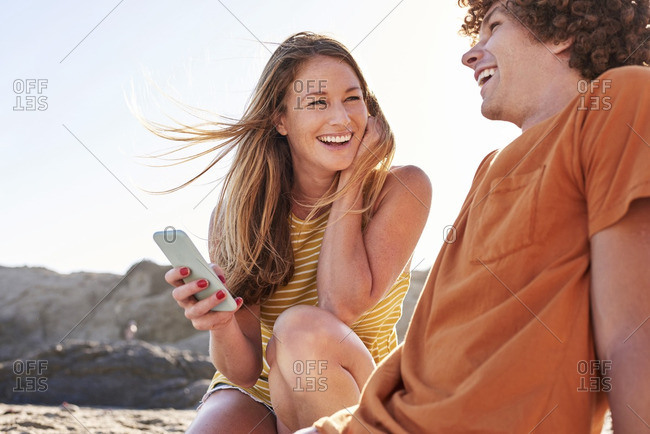 Happy couple with cell phone on the beach