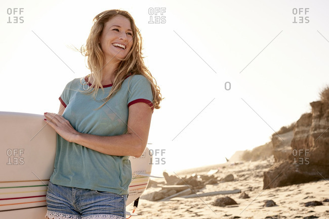 Happy woman carrying surfboard on the beach