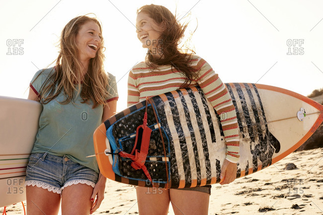 Two happy women carrying surfboards on the beach
