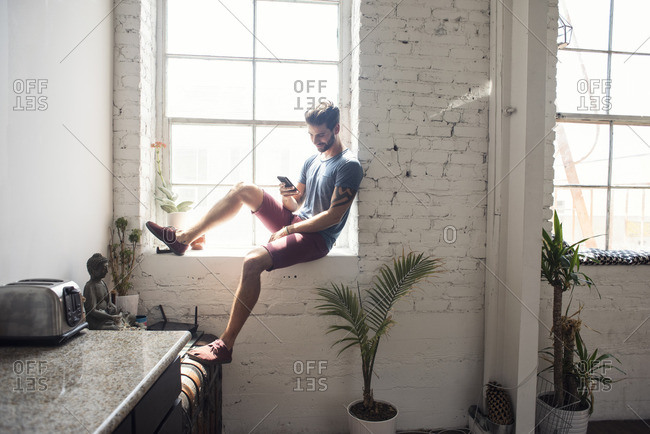 Young man sitting on windowsill looking on cell phone in a loft