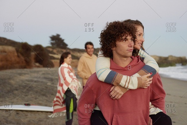 Young man carrying girlfriend piggyback on the beach