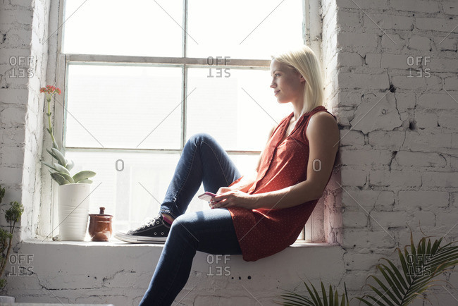 Young woman sitting on windowsill in a loft