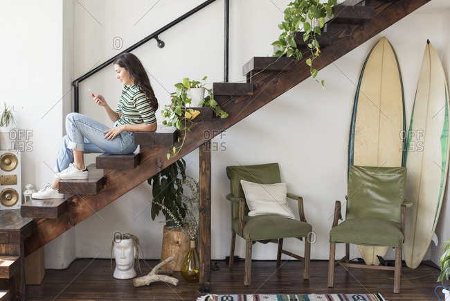 Young woman sitting on stairs in a loft looking at cell phone
