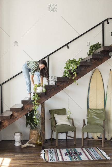 Young woman on stairs in a loft caring for potted plant