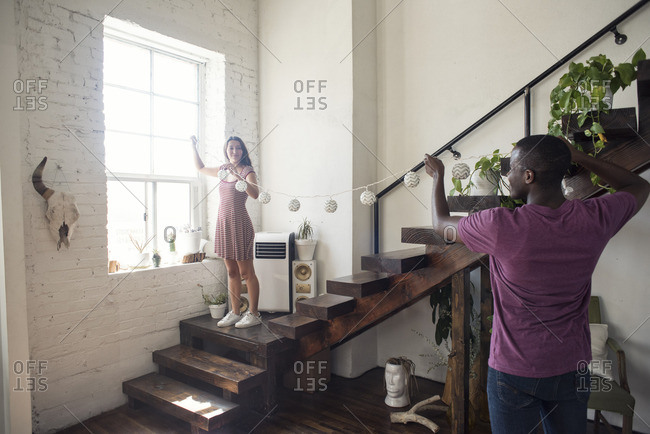 Young couple decorating loft with fairy lights