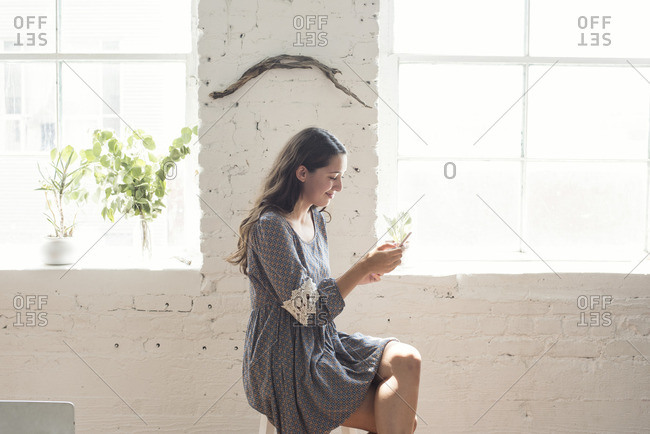 Smiling young woman looking on cell phone in a loft
