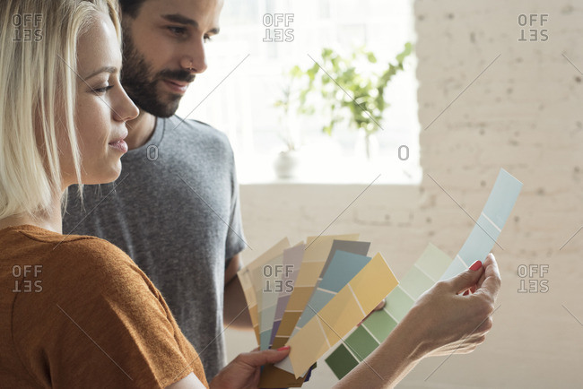 Young couple in a loft looking at color samples