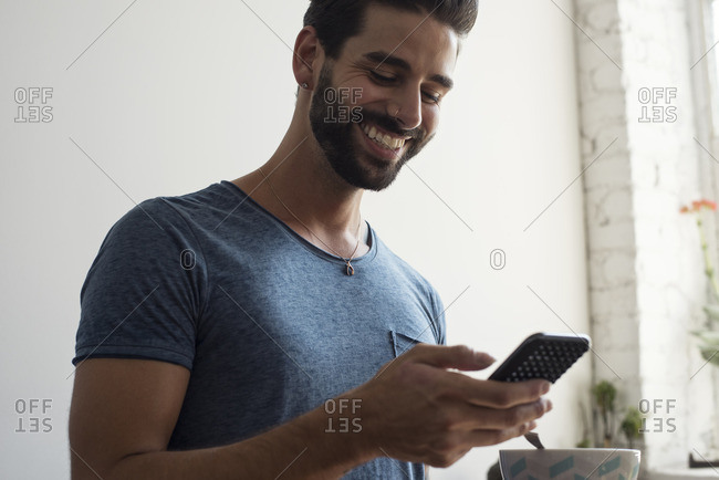 Smiling young man looking on cell phone