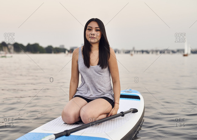 Germany- Hamburg- Young woman on paddleboard enjoying summer
