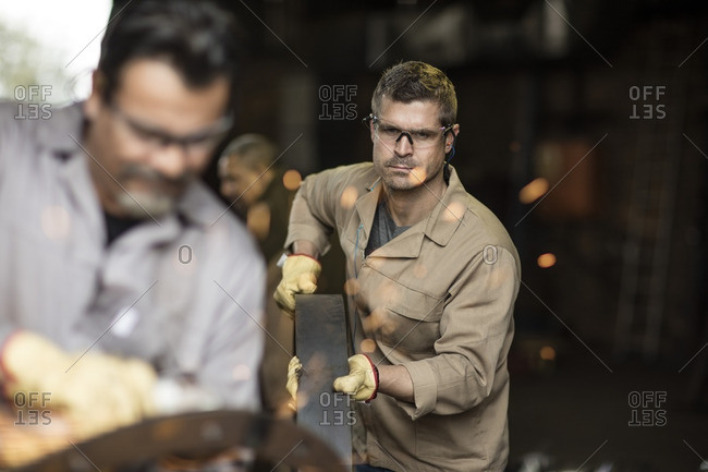 Steel workers in metal construction factory