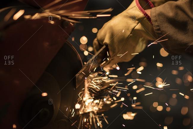 Metal worker using grinding machine in factory workshop