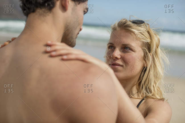 Tender young couple standing on the beach