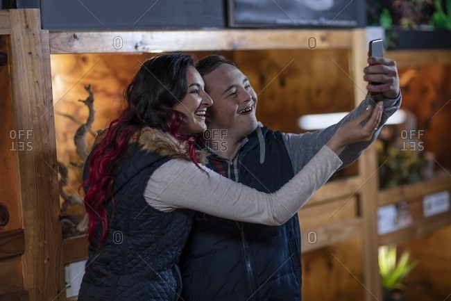 Young man with down syndrome and young woman taking a selfie at reptile exhibition