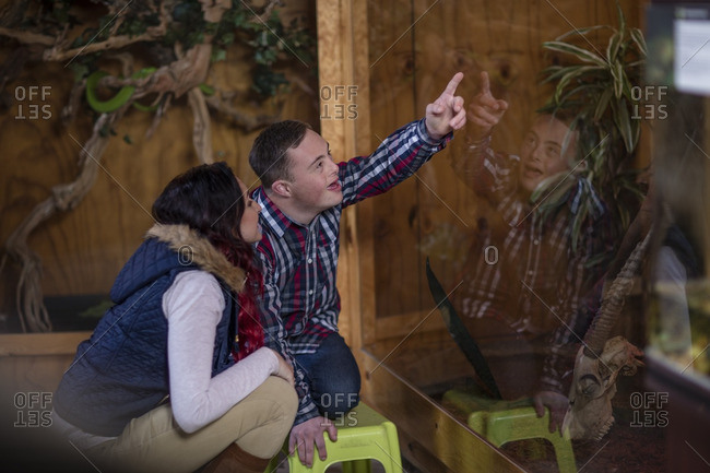 Young man with down syndrome and young woman visiting reptile exhibition