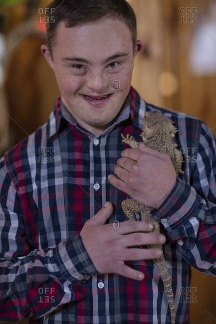 Young man with down syndrome holding a bearded dragon